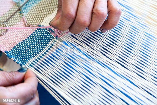 Close Up Hand of Woman Worker Use Needle for Weaving Loom Linen to Weaving machine and Thai traditional Linen.  A homemade Linen textile in Thailand