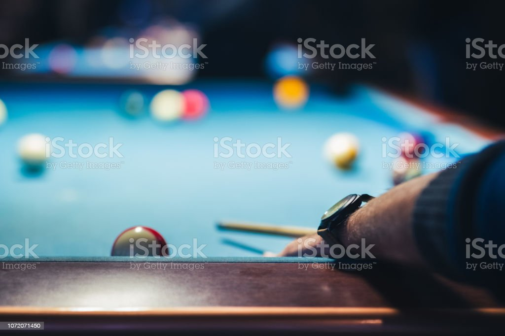 Close up hand of young man playing billiard game.