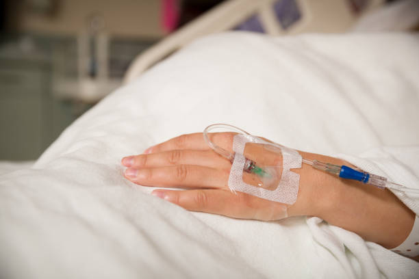 close up hand of young patient with intravenous catheter for injection plug in hand during lying in the hospital bed. - catetere foto e immagini stock
