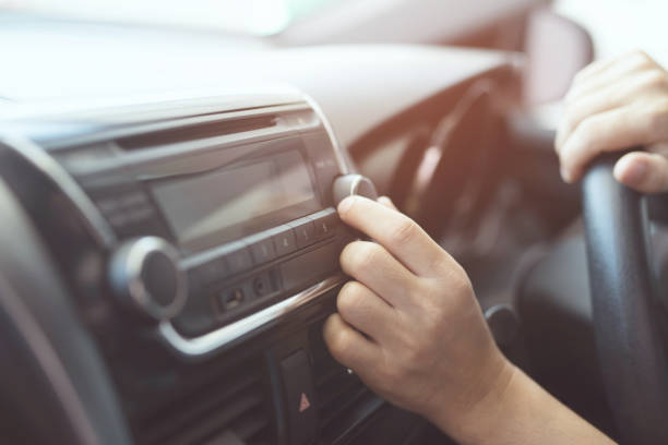 close up hand open car radio listening. car driver changing turning button radio stations on his vehicle multimedia system. modern touch screen audio stereo system. transportation and vehicle concept - radio foto e immagini stock