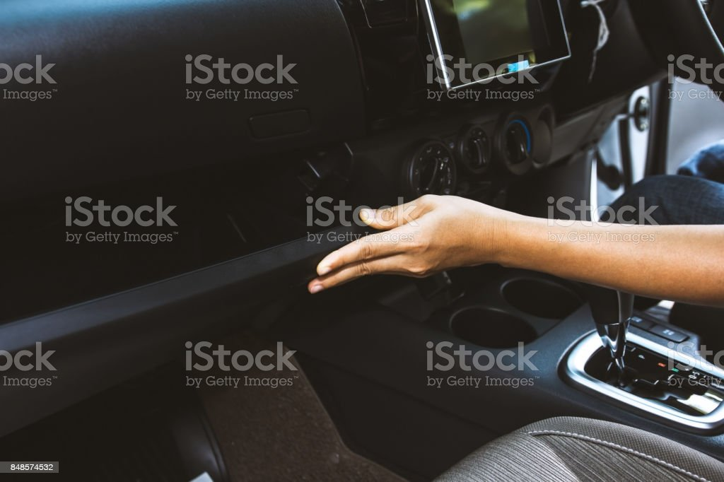 Close up hand opening glove compartmet in car stock photo