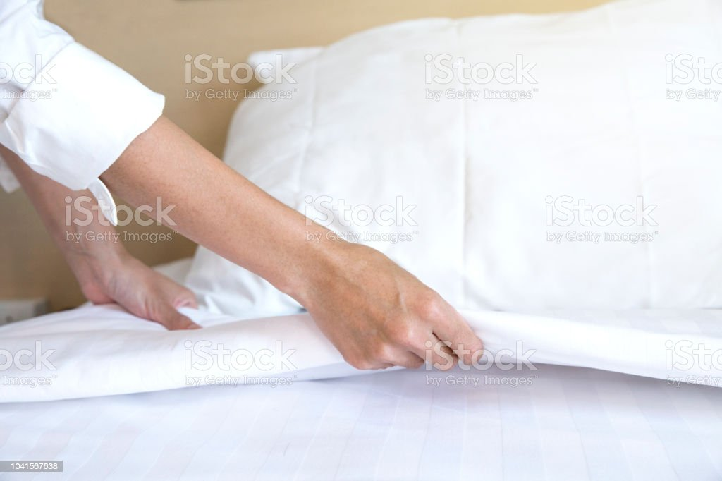 Close up hand set up white bed sheet in hotel room