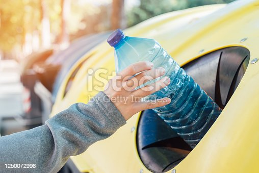 istock Close up hand throwing empty plastic bottle into the trash 1250072996