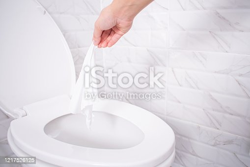 Close up hand throwing toilet paper to the toilet in a white tile bathroom.