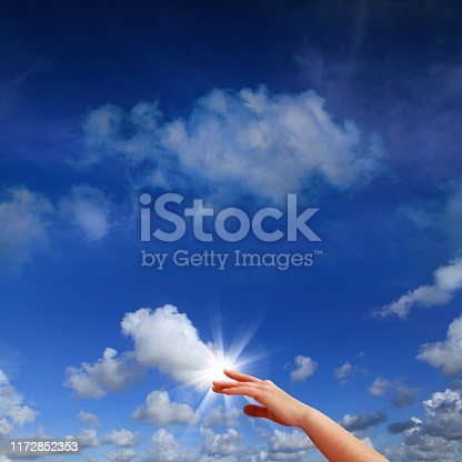 Conceptual internet image of close up hand touching clouds in blue sky