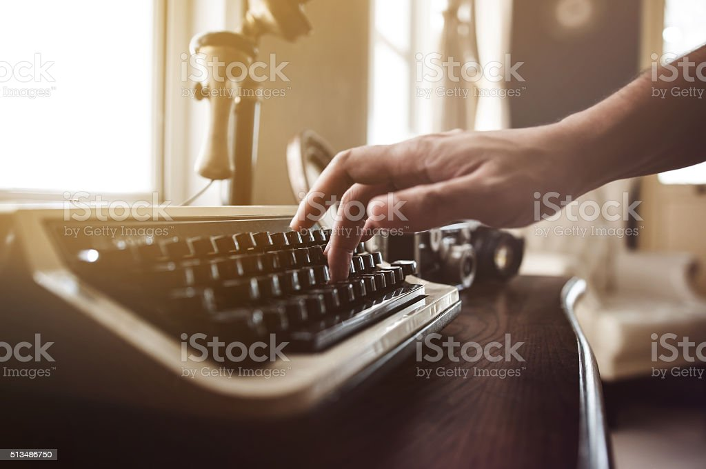 Close up, Hand typing on an old typewriter stock photo