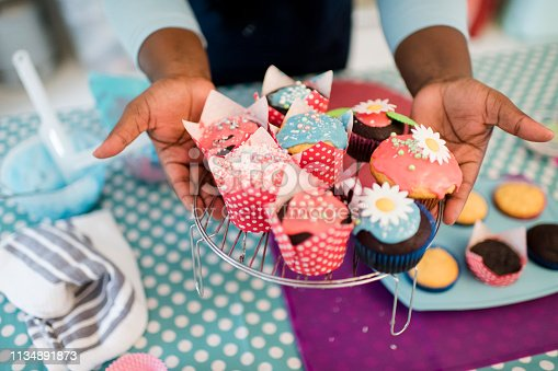 Close up hands hold out brightly decorated homemade cupcakes