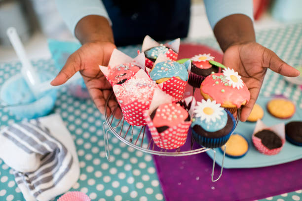 Close up hands hold out brightly decorated homemade cupcakes stock photo