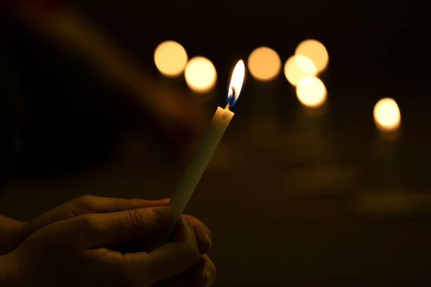 Close up hands  lighting candle vigil in darkness.Concept of light of hope., worship, prayer.soft focus