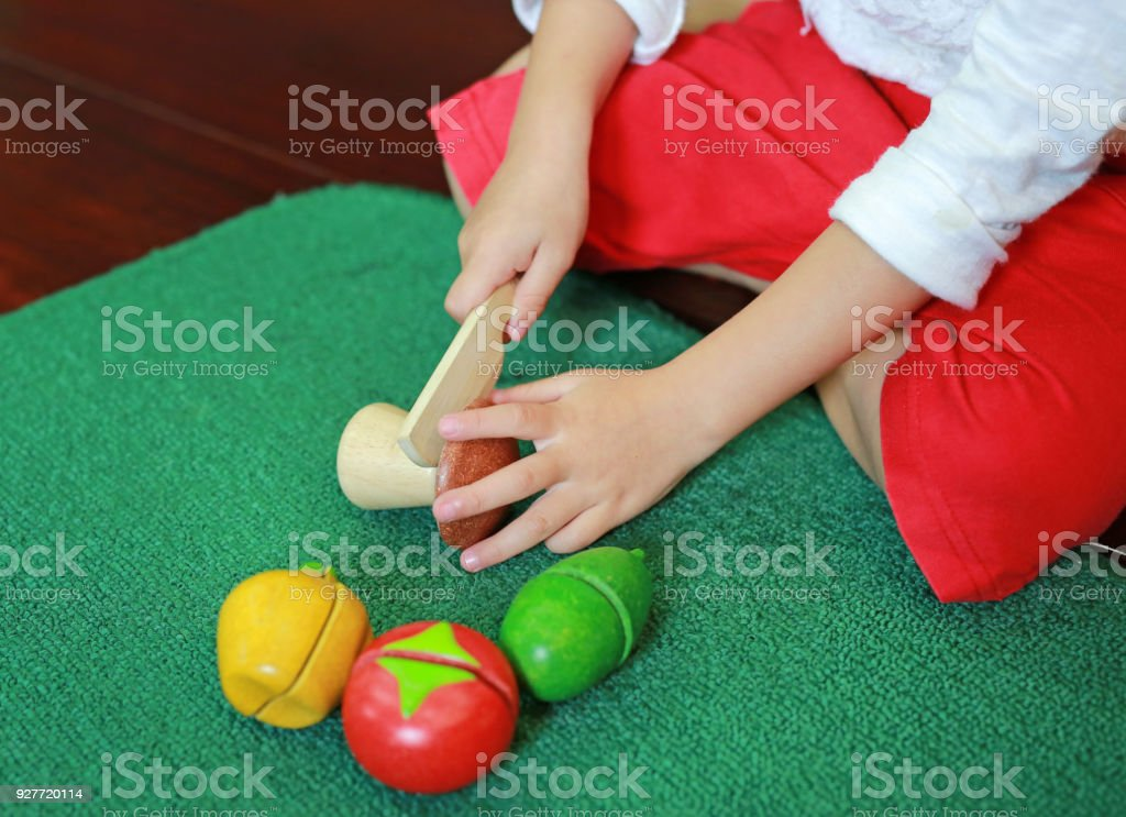 Close up hands of asian child girl playing wooden cooking toy. stock photo