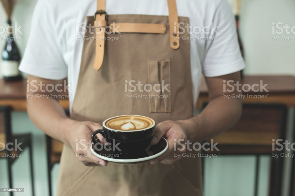 Close up hands of barista man holding cup of hot latte coffee in the cafe stock photo
