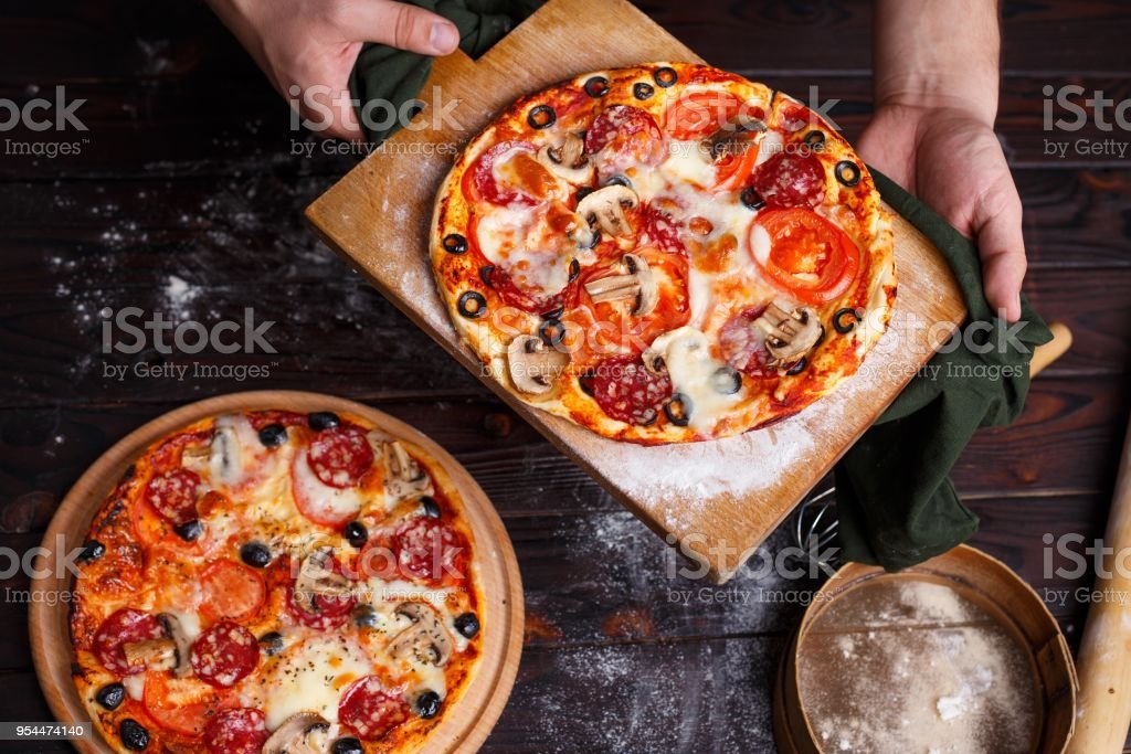 Close up hands of chef baker holding a board with hot freshly ba stock photo