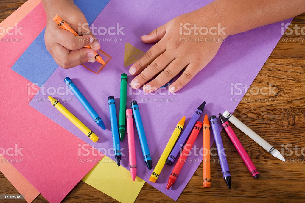 Close up hands of child drawing with colorful crayons stock photo
