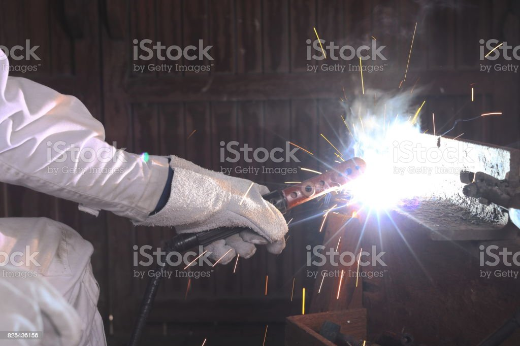 Close up hands of industrial worker with torch and protective gloves welding steel with spark in the factory. stock photo