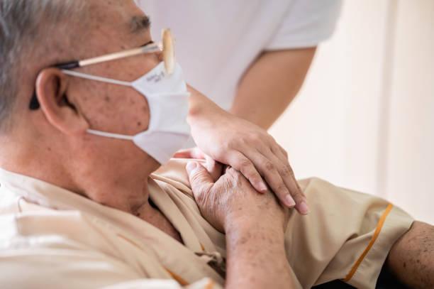 närliggande händer läkare eller kusin familj försiktigt hålla senior patientens händer bär ansiktsmask för att förhindra virusinfektion i komfort och konsol under återhämtning på sjukhus. - emotionellt stöd bildbanksfoton och bilder