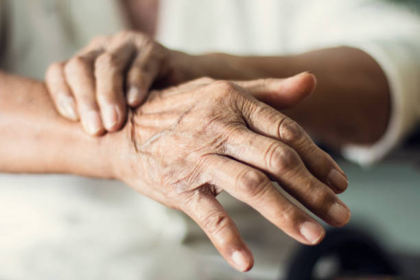 Close up hands of senior elderly woman patient suffering from pakinson's desease symptom. Mental health and elderly care concept stock photo