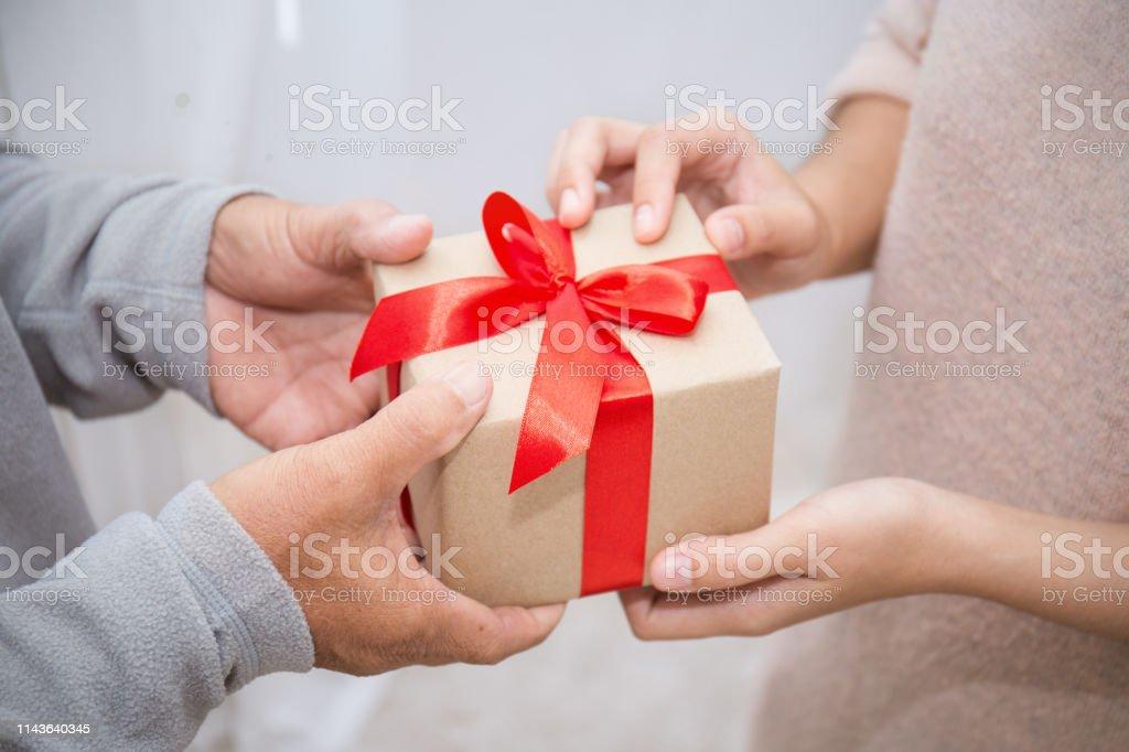 年配の男と彼の娘のギフトボックスを与えるの手を閉じます。ボクシングデーホリデーバースデークリスマスの日のコンセプト ストックフォト