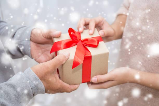高齢の老人と雪の背景を持つギフトボックスを与える彼の娘の手を閉じます。ボクシングデーホリデーバースデークリスマスの日のコンセプト ストックフォト