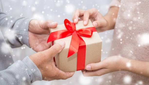 雪の背景を持つギフトボックスを与える先輩の老人と彼の娘の手をクローズアップ。ボクシングデーホリデー誕生日クリスマスの日のコンセプト ストックフォト