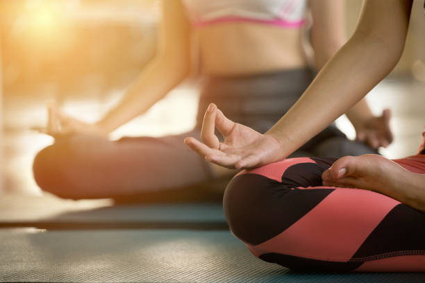 close up hands of  woman doing yoga exercising meditation . group of girl meditate sitting in lotus position on mat fingers in mudra at fitness gym sport club in sunrise - yoga imagens e fotografias de stock