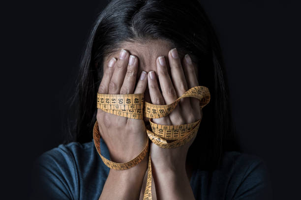 close up hands wrapped in tailor measure tape covering face of young depressed and worried girl suffering anorexia or bulimia nutrition disorder on black background stock photo