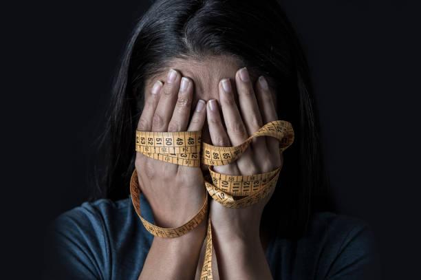 close-up van handen gewikkeld in kleermaker maatregel tape die betrekking hebben op gezicht van depressief en bang meisje lijden anorexia of boulimia voeding stoornis op zwarte achtergrond - lichaamsbewustzijn stockfoto's en -beelden