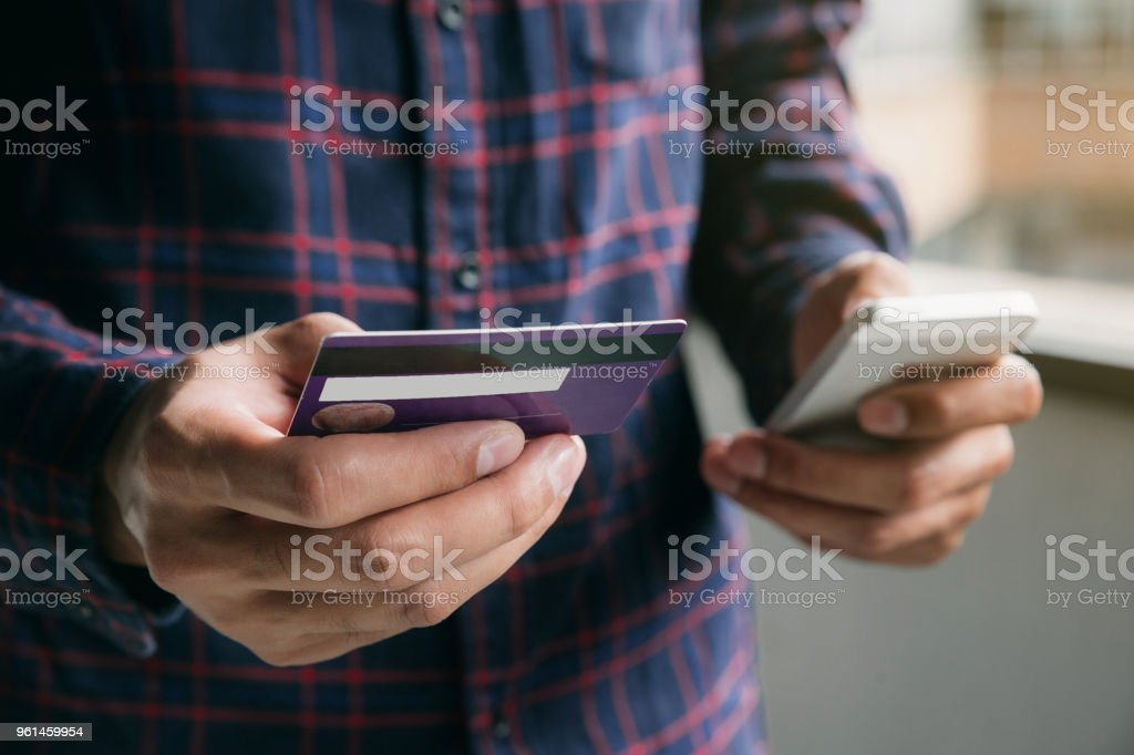 Close Up hands young man holding credit card with smart phone and...