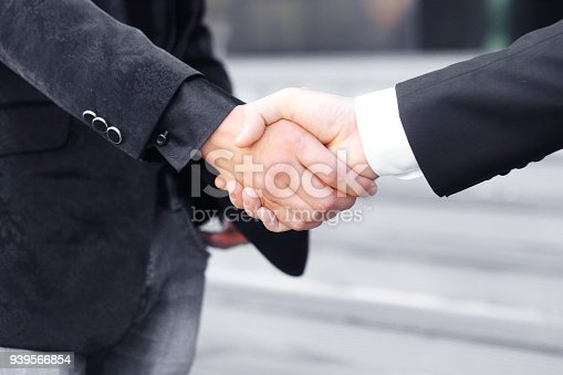 istock close up. handshake business partners on blurred background 939566854