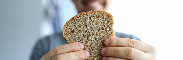 Close up happy guy holds piece whole grain bread. Healthy eating during self-isolation. Making homemade wholesome whole grain bread. Changing eating habits. Man bakes yeast-free bread