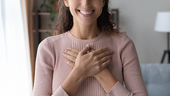 Close up focus on happy sincere female holding folded hands on chest. Emotional positive kind candid millennial woman feeling thankful indoors, showing gratitude sign, believe faith charity concept.