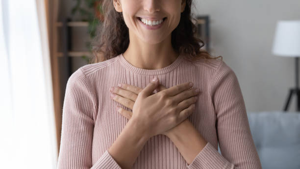 Close up happy sincere female holding folded hands on chest. Close up focus on happy sincere female holding folded hands on chest. Emotional positive kind candid millennial woman feeling thankful indoors, showing gratitude sign, believe faith charity concept. love emotion stock pictures, royalty-free photos & images