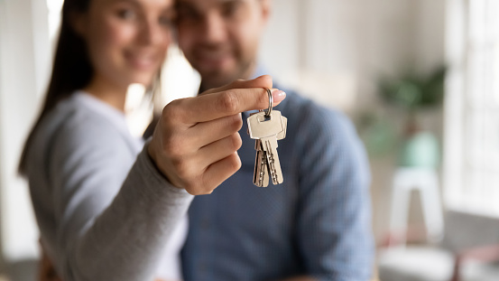 Close up happy woman hugging man, holding keys from new first house, young family celebrating moving day, satisfied customers couple purchase real estate, mortgage and relocation concept