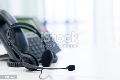 close up headset of call center and VOIP for communication technology on office table  in monitoring room for network operation job concept