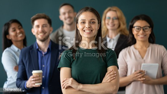 Close up headshot portrait of happy businesswoman hands crossed posture. Different age and ethnicity businesspeople standing behind of female company chief business. Leader of multi-ethnic team concept