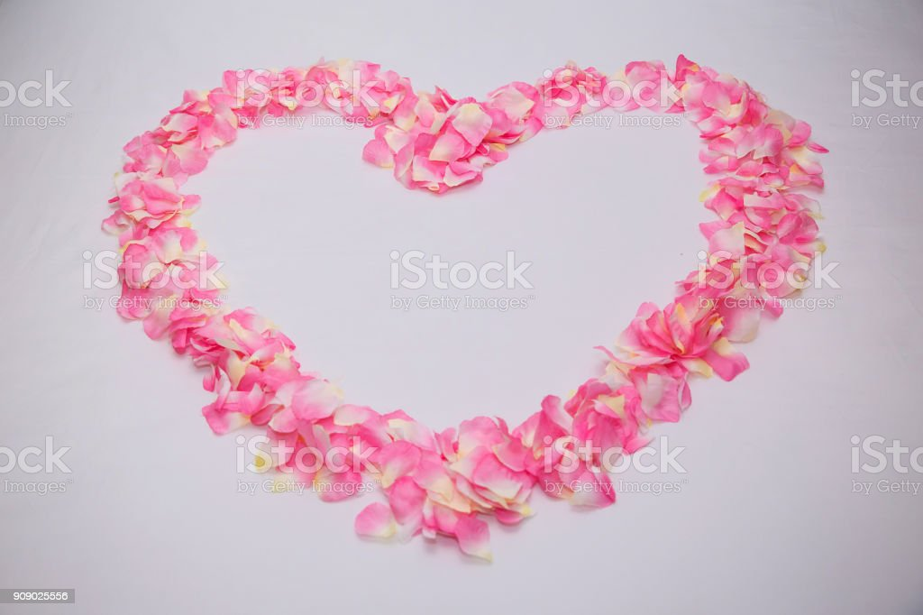 Close up heart shape from pink rose petals on the white bed. honeymoon suite room decoration. stock photo
