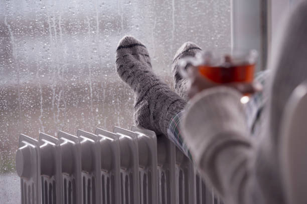 Close up heating female feet with woolen socks on the radiator heater. The woman drinking hot tea. stock photo