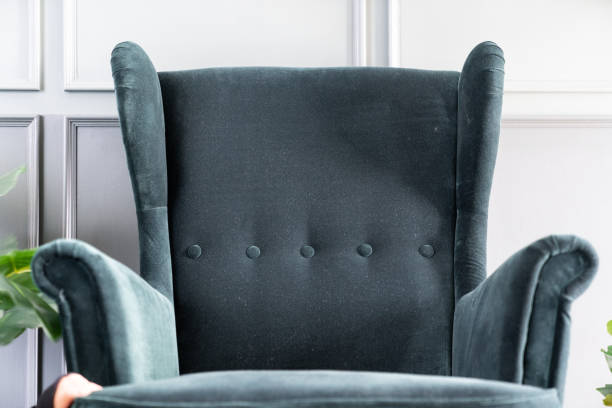 Close up high back green velvet armchair with gray painted wall in the background / interior concept / empty space for advertising Close up high back green velvet armchair with gray painted wall in the background / interior concept / empty space for advertising zoom effect stock pictures, royalty-free photos & images