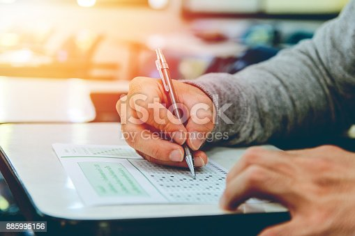 istock Close up , High School male student holding pencil exams writing in classroom for education test ,Copy space for your text.Vintage tone with sunset light ,Education concept. 885995156
