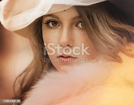 Close up portrait of a beautiful woman in a hat, with white fur on her shoulders, looks directly into the camera. Historical reconstruction