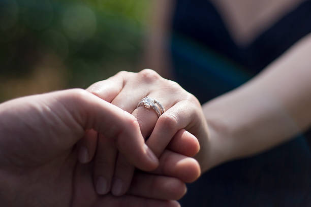 Close Up Holding Hands with Engagement Ring stock photo