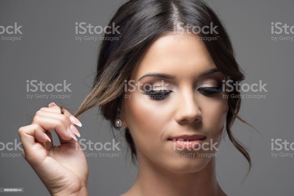 Close up horizontal portrait of young woman face with bun hairstyle holding hair lock looking down serious stock photo