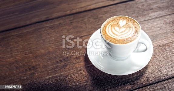 Close up hot cappuccino white coffee cup with heart shape latte art on dark brown old wood table at cafe,food and drink concept