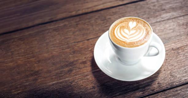 zamknij gorącą filiżankę kawy cappuccino z kształtem serca latte art na ciemnobrązowym starym drewnianym stole w kawiarni, koncepcji jedzenia i picia. - coffee zdjęcia i obrazy z banku zdjęć