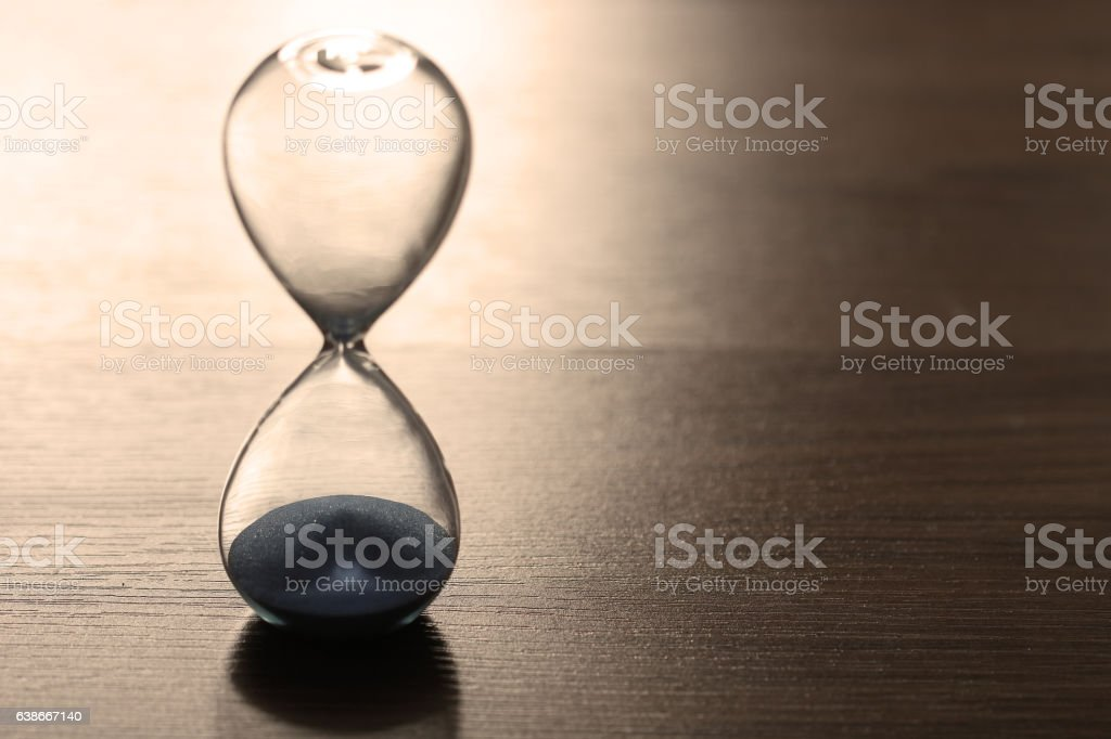 Close up hourglass on wooden floor for time concept stock photo