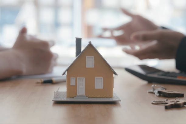 Close up house model on blur background of real estate agent and customer stock photo