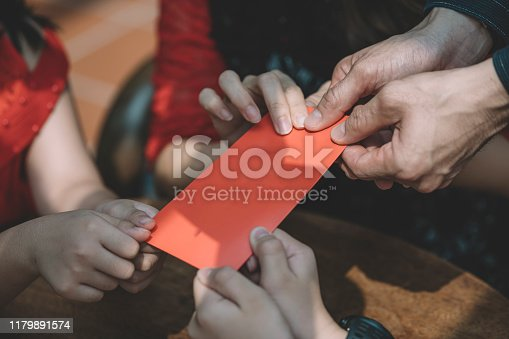 close up human hand giving ang pao , red envelope to children in the family as tradition