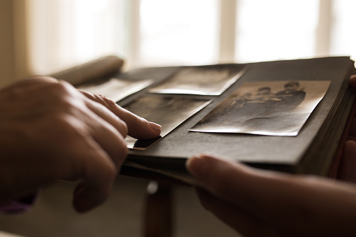 Close up unrecognizable person looking photo album pointing to one photo
