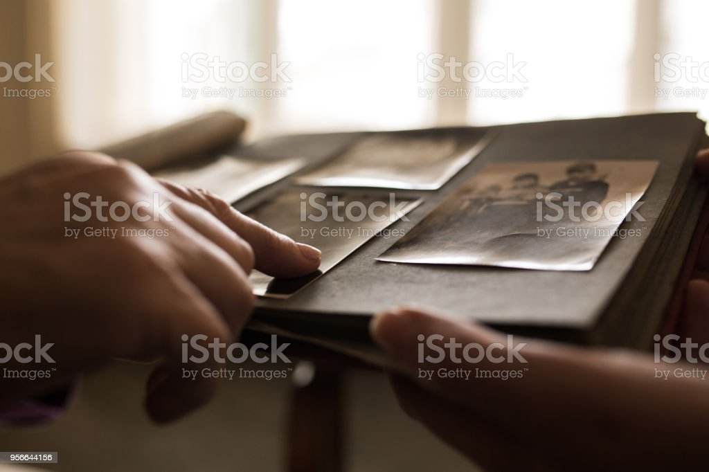 Close up human hand pointing to photo in photo album stock photo