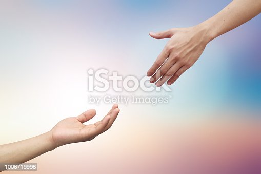 istock close up human hand receiving or blessing something with god hand outstretch for helping on blurred colorful sunrise sky for religion and believe concept 1006719998