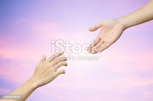istock close up human hand receiving or blessing something with god hand outstretch for helping on blurred colorful sunrise sky for religion and believe concept 1035928092